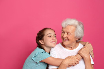 Cute girl hugging her grandmother on pink background