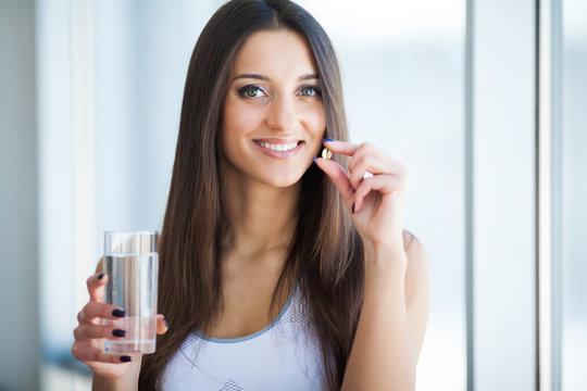 Beautiful Smiling Woman Taking Vitamin Pill. Dietary Supplement