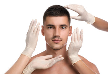 Doctors examining man's face for cosmetic surgery on white background