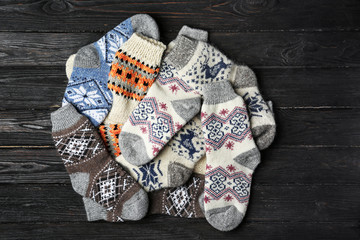 Fototapete - Different knitted socks on black wooden background, flat lay