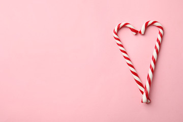 Fotobehang - Flat lay composition with candy canes on pink background. Space for text