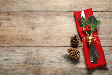 Cutlery set on wooden table, top view with space for text. Christmas celebration