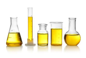 Fototapete - Laboratory glassware with yellow liquid on white background