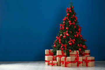Fotobehang Bomen Decorated Christmas tree and gift boxes near blue wall. Space for text