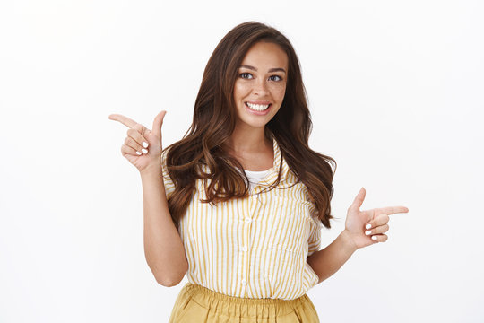 Satisfied cute woman with freckles, dark hair, smiling cheerful, pointing fingers sideways, show left and right copy space, grin impressed, recommend friends cool places to visit, white background