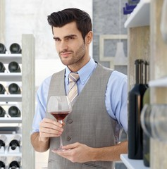 Young man holding glass of red wine
