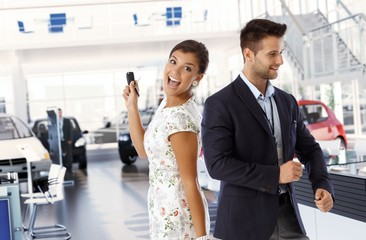 Happy lady with new car keys at dealership indoors
