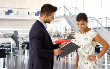 Young woman at car dealership reviewing papers