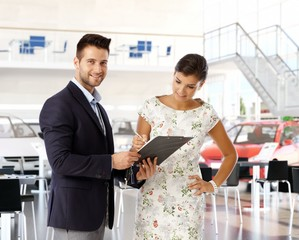 Woman signing business contract at car dealership
