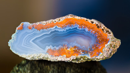 Cross-section by polished agate with beautiful wavy pattern on smooth cut surface. Blue gem detail with uneven rusty border and mirroring on shiny dark background. Silica item from north-east Bohemia.