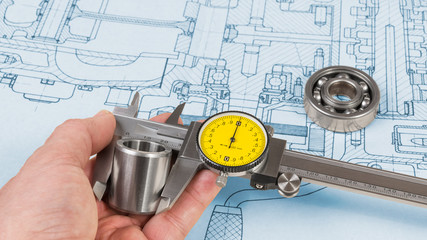 Steel part measurement by caliper in human hand. Ball bearing on technical drawing of combustion engine. Quality control. Engineer when measuring a metal roller diameter by precise tool. Project plan.