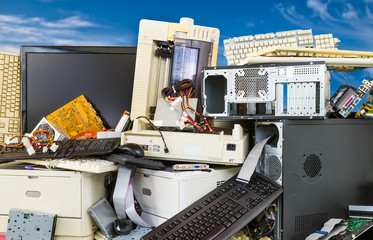 Electronic, plastic and metal waste on a dump of discarded computer components. Pile of obsolete hardware PC parts on blue sky background. Sorting and recycling refuse. Environmental pollution danger.