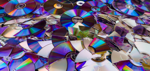 Broken compact discs. Colorful texture detail of obsolete digital media. Data backup, archiving or eco disposal. Old damaged optical storage devices on e-waste heap. Rainbow reflection on shiny disks.