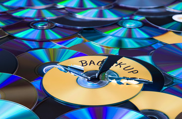 Damaged compact disc. Secure backup and disposal of digital personal data. Old broken optical storage device on green-blue texture. Shredding of discarded obsolete archiving media. Shiny e-waste heap.