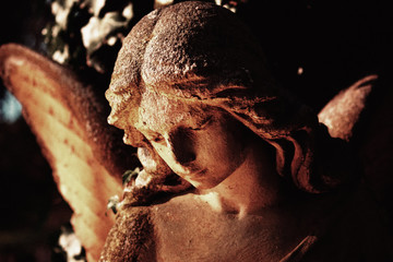 Fototapete - Photo of ancient angel statue. Deep shadows for expression