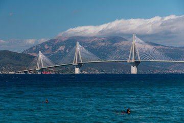 Bright blue ocean with mountains and a bridge in the background and people swimming in the water.