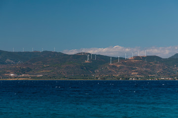 A mountain range in Greece with the ocean in the foreground and wind towers on the hill.
