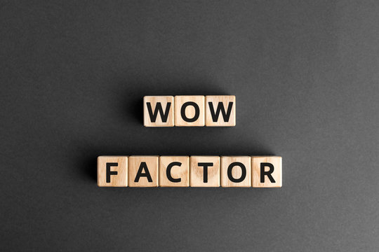 Wow factor - words from wooden blocks with letters, extremely impressive or attractive, wow factor concept, gray background
