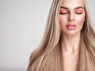 Portrait of a beautiful woman with a coral color makeup. Attractive blond  girl with  bright...