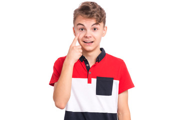 Poster - Portrait of smiling teen boy showing his eye. Child pointing with finger to eye. Caucasian young teenager, isolated on white background. Eyesight control. Medicine, people and health concept.