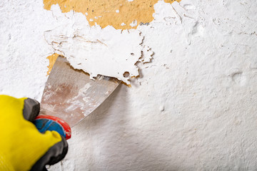 Removing old paint from the wall with a metal spatula. Small painting works at home.