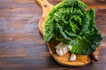 Fresh raw savoy cabbage on wooden background