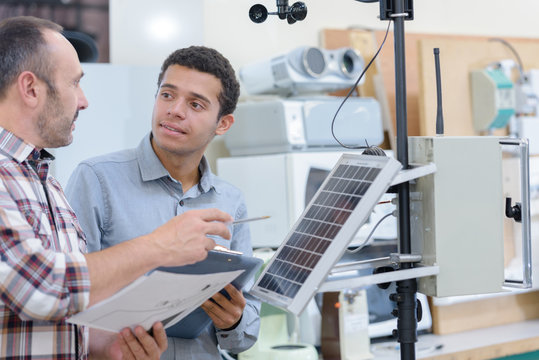 two people working on solar panels