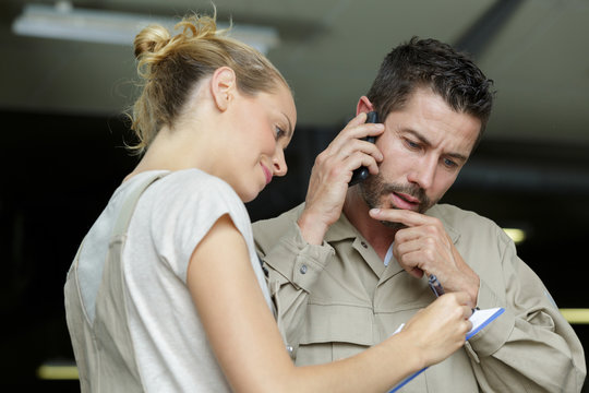 worker talking on phone while female colleague writing on clipboard
