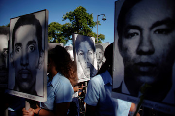 Students and family members of the 73 people killed in the 1976 downing of a Cuban airliner in Barbados hold pictures of the victims while attending a memorial ceremony at the Colon cemetery in Havana