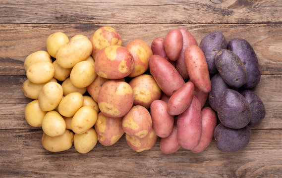 Heap of different types of potatoes on wooden rustic table