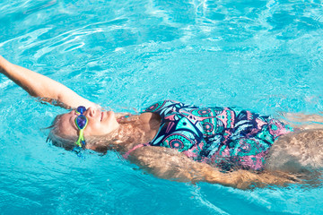 Foto auf AluDibond Tauchen A senior woman with blue swimming pool goggles swims in the transparent water of the swimming pool. Healthy activity for pensioner. Lifestyles