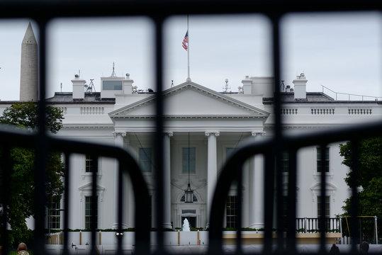 The White House is seen through a metal gate in Washington