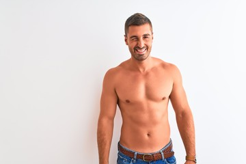 Young handsome shirtless man showing muscular body over isolated background winking looking at the camera with sexy expression, cheerful and happy face.