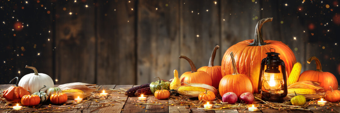 Wooden Table With Lantern And Candles Decorated With Pumpkins, Corncobs, Apples And Gourds With Wooden Background - Thanksgiving / Harvest Concept