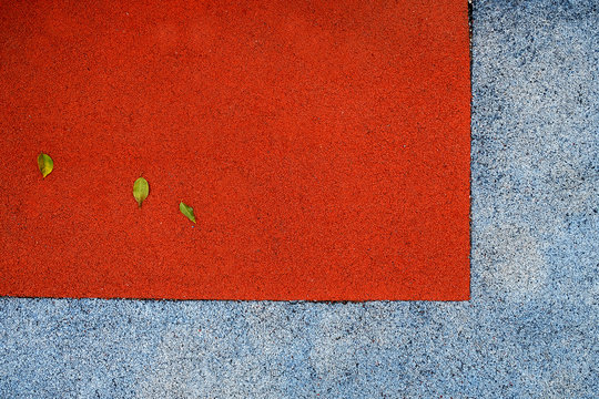 A corner of a red and white city playground with three small leaves on its surface.