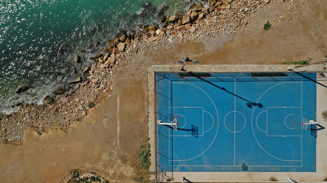 Aerial top down photo of outdoor basketball court by the sea in Piraeus area, Attica, Greece