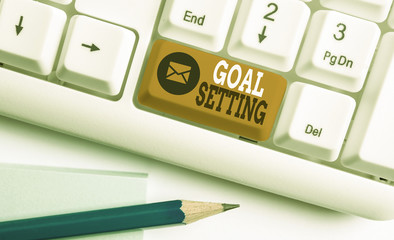 Conceptual hand writing showing Goal Setting. Concept meaning process of identifying something that you want to accomplish White pc keyboard with note paper above the white background