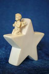 Betender Engel auf weißem Stern vor blauem Hintergrund