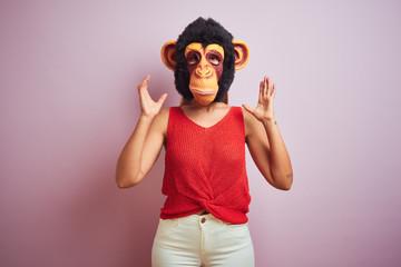 Woman standing wearing t-shirt and monkey mask
