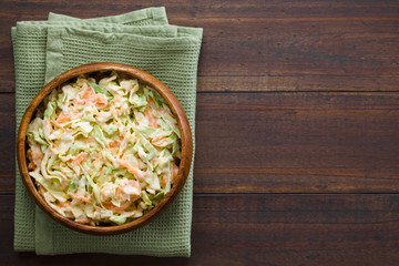 Coleslaw made of freshly shredded white cabbage and grated carrot with homemade mayonnaise-based salad dressing, photographed overhead with copy space on the side (Selective Focus, Focus on the salad)