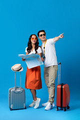 Tourist couple with baggage in blue studio background