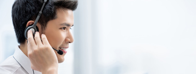 Asian man wearing headphones working in call center