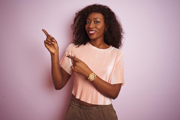 Young african american woman wearing t-shirt standing over isolated pink background smiling and looking at the camera pointing with two hands and fingers to the side.