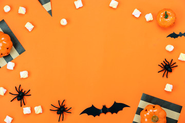 Table top view aerial image of decorations Happy Halloween day background holiday concept.Flat lay objects to party pumpkins and spider with candy sweet on orange  paper.Copy space for creative design