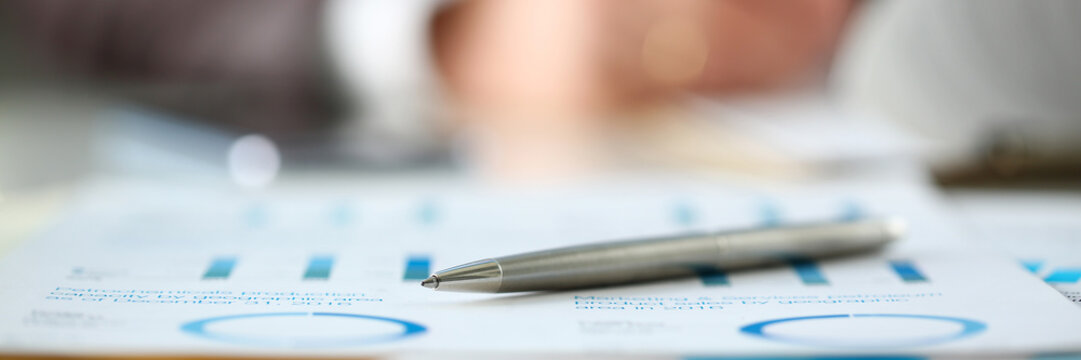 Silver pen lie at important paper on table in office closeup with businessman in background. Paperwork job trade balance bank credit loan money invest payment irs commerce partnership concept