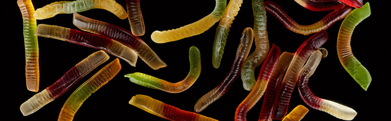 top view of colorful gummy worms isolated on black, Halloween treat