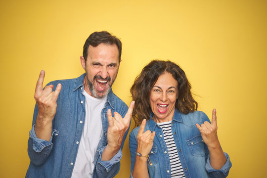 Beautiful middle age couple together wearing denim shirt over isolated yellow background shouting with crazy expression doing rock symbol with hands up. Music star. Heavy concept.