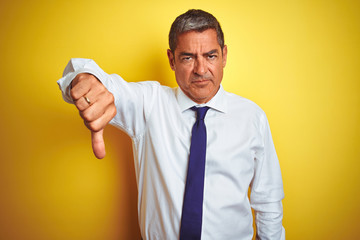 Handsome middle age businessman standing over isolated yellow background looking unhappy and angry showing rejection and negative with thumbs down gesture. Bad expression.
