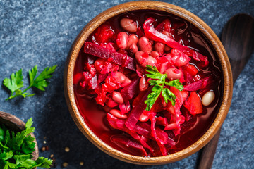 Vegetarian beetroot soup borsch with beans in a wooden bowl on blue background. Healthy vegetarian food concept.