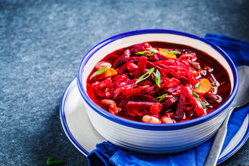 Vegetarian beetroot soup borsch with beans in white bowl on blue background. Healthy vegetarian food concept.